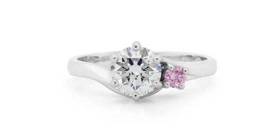 センターダイヤの片サイドに大きめのピンクダイヤ  を添えたプラチナ婚約指輪