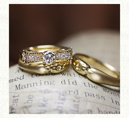 ネコの手のデザインのゴールド結婚指輪とリボンゴールドの婚約指輪を重ねてセットリングに