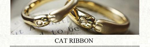 ネコの手がリボンカチューシャのように デザインされたゴールドのペアリング