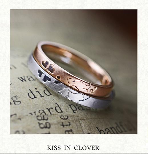 ピンクのネコと白いネコが クローバーの中でキスする結婚指輪