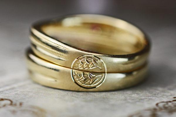 結婚指輪を重ねて両家の家紋を作りあげるゴールドのペアリング