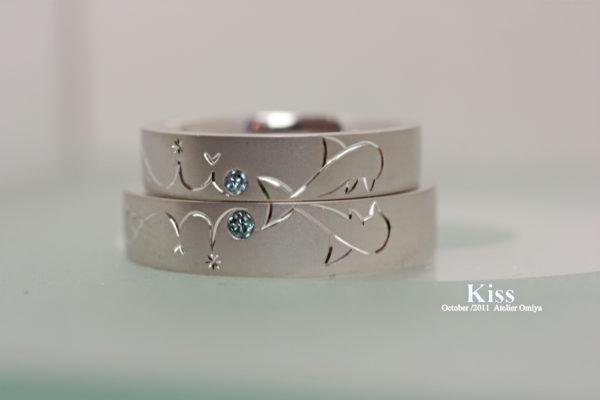二本重ねてイルカがキスする結婚指輪