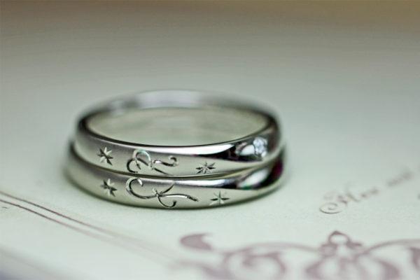 結婚指輪の横でイニシャルtとRハートをつくったオーダーメイドリング