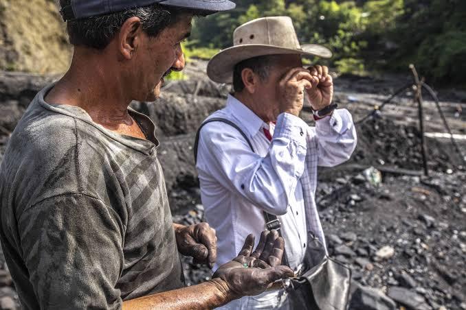 ルーペ片手に、エメラルドの鉱石を見て現金を渡している現地買い付け人