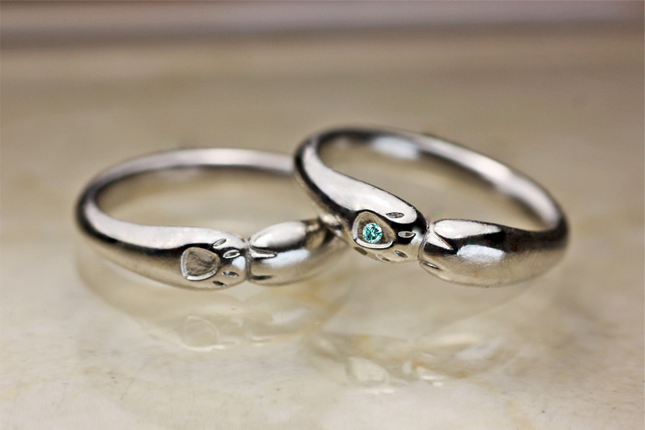 ネコの結婚指輪の手の模様の中にブルーダイヤモンドをセットしたもの