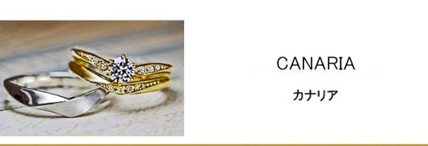 指にとまったカナリアのゴールドの婚約指輪と結婚指輪セットリング