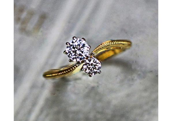 2つのダイヤモンドがウェーブしたゴールドリングに並ぶ婚約指輪
