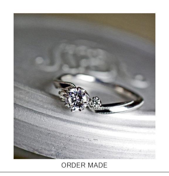 【リボン】をひねったデザインにミルグレインをあしらった婚約指輪作品