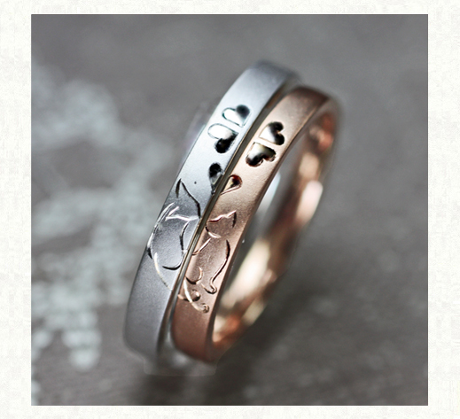 ピンクのネコと白いネコが クローバーの中でキスする結婚指輪オーダーメイド