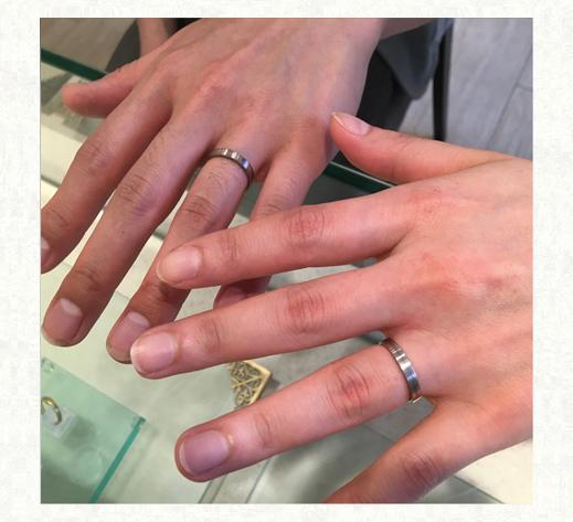 白とグレーのモノトーンデザインの結婚指輪 お客様の指にリングをつけて