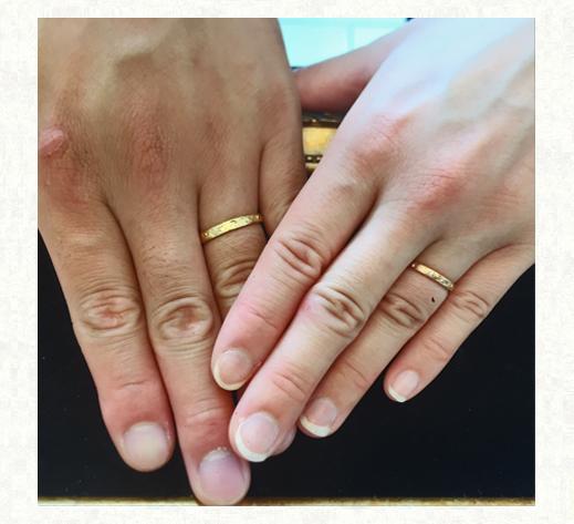 イニシャルが花模様の中に入った ピンクとゴールドとイエローゴールドの結婚指輪をされたお客様の手の写真 千葉・柏 ヨーアンドマーレ