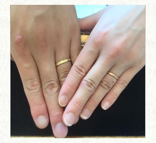 ゴールドの結婚指輪をつけたお客様の手