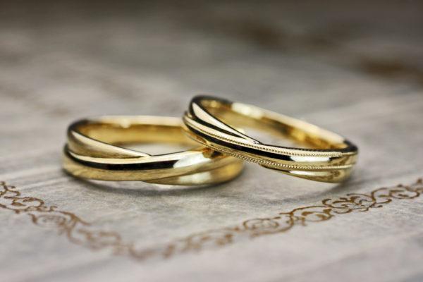 センターでクロスしたデザインのゴールドの結婚指輪