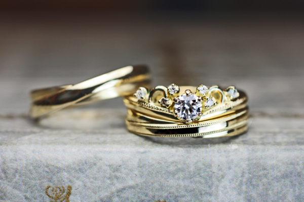 ティアラデザインのゴールド婚約指輪とクロスしたデザインの結婚指輪の3本セット