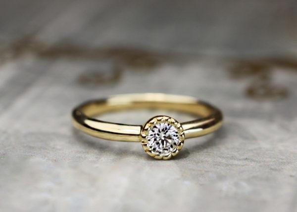 ダイヤモンドをミルグレインで囲ったゴールドの婚約指輪