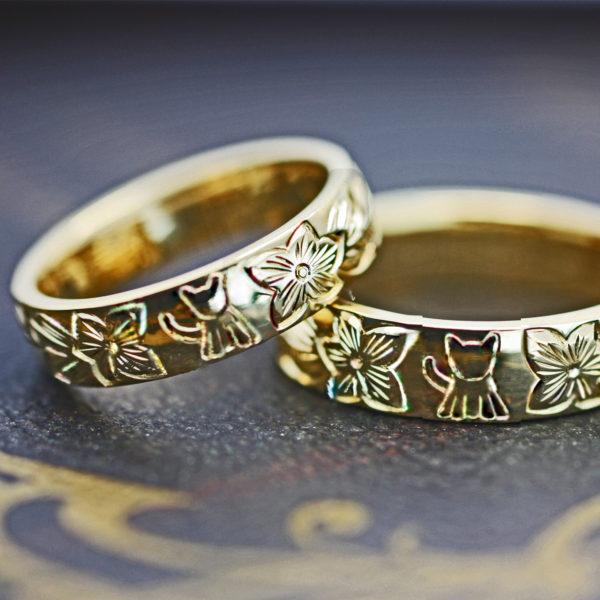 ハワイアン模様にネコがデザインされたゴールドのオーダー結婚指輪