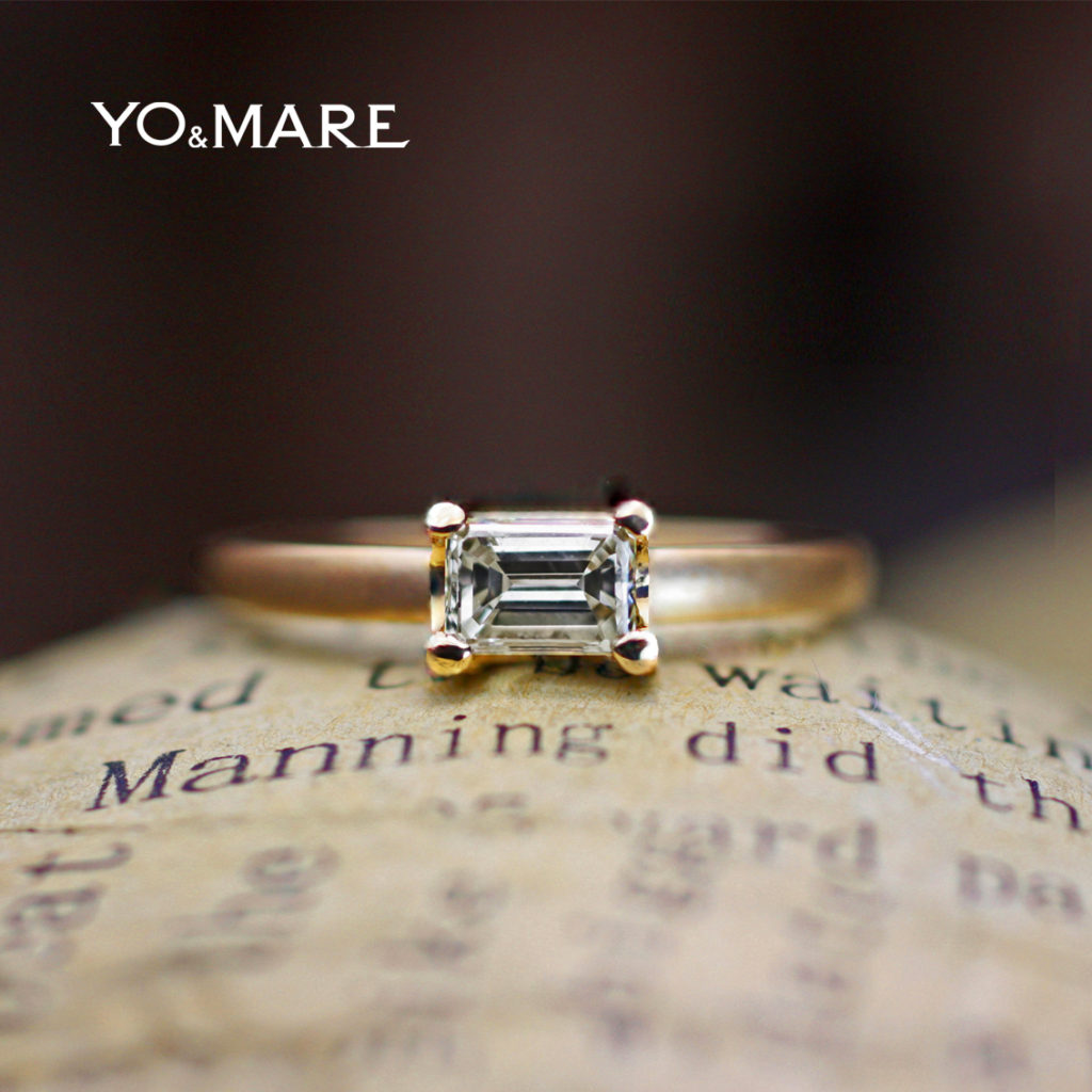 エメラルドカットのダイヤモンドをマットゴールドでつつんだ婚約指輪