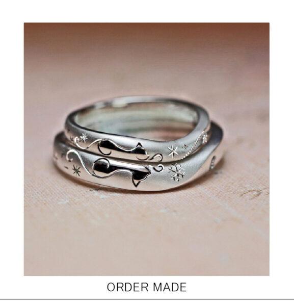二匹のネコが向かい合わせでハートを作った結婚指輪のオーダーリング >>