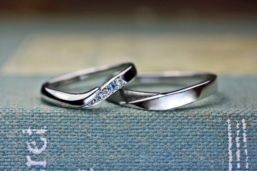 ダイヤが並んでだ中にブルーの石がある結婚指輪
