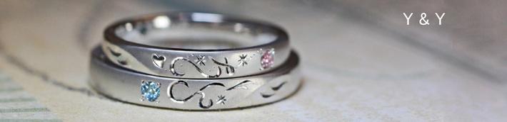 ふたつの結婚指輪でイニシャルを重ねてハートをつくる天使たちのリング