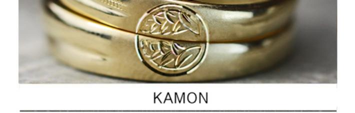 結婚指輪を重ねて両家の家紋を作りあげるゴールドのペアリングの画像